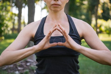 cropped image of woman meditating and making gesture with hands in park