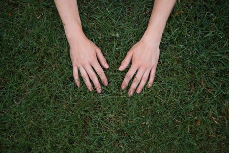 cropped image of woman touching green grass with hands in park
