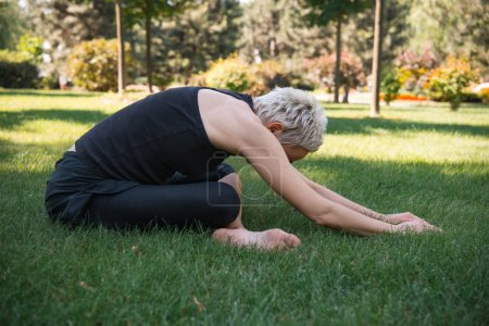 side view of woman practicing yoga in Extended Child pose (Utthita Balasana) on grass in park