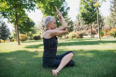 side view of woman practicing yoga and sitting on grass in park