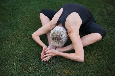high angle view of woman practicing yoga on grass in park