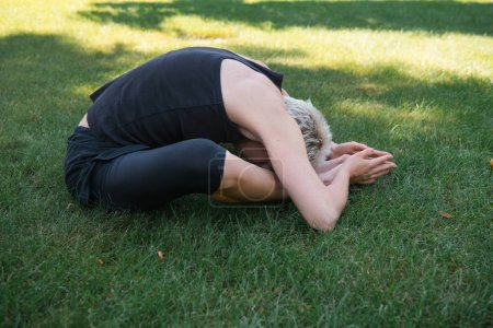 side view of woman practicing yoga on grass in park