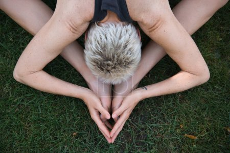 top view of woman practicing yoga on grass in park