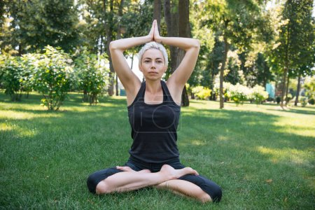 woman practicing yoga in lotus pose with raised hands making namaste gesture on grass in park