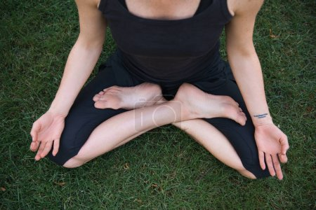 cropped image of woman practicing yoga in lotus pose and meditating on grass in park
