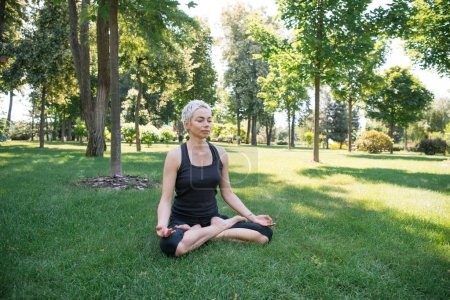 woman practicing yoga in lotus pose and meditating on grass in park