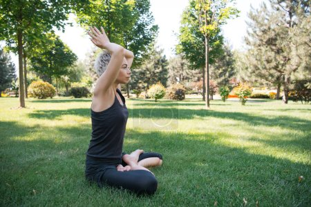 side view of woman practicing yoga in lotus pose with raised hands making namaste gesture on grass in park