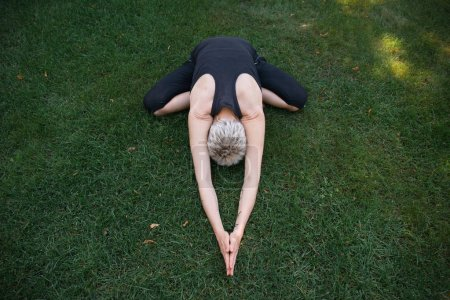 high angle view of woman practicing yoga in Wide Child pose (Balasana) on grass in park