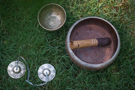 tibetan singing bowls on green grass in park