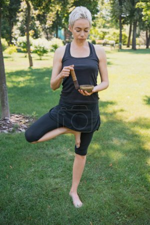 woman practicing yoga in tree pose and making sound with tibetan singing bowl in park