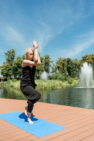 woman practicing yoga and standing on one leg on yoga mat near river in park