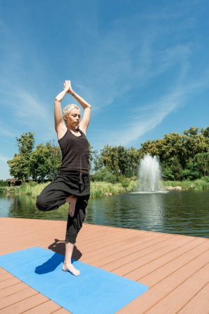Photo for Woman practicing yoga in Tree pose (Vrksasana) on yoga mat near river in park - Royalty Free Image