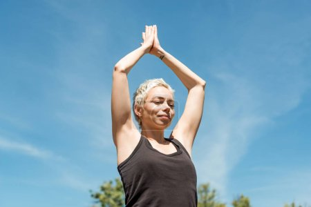 low angle view of woman practicing yoga in Tree pose (Vrksasana) in park