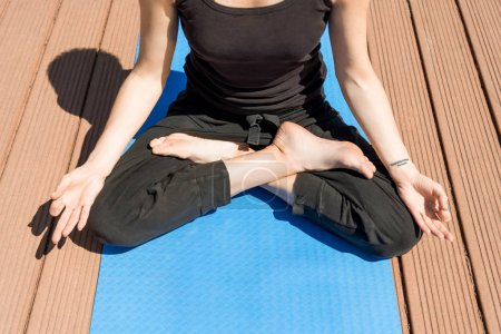 cropped image of woman practicing yoga in lotus pose on yoga mat