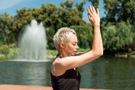 Photo for Side view of woman practicing yoga with hands in namaste gesture near river in park - Royalty Free Image