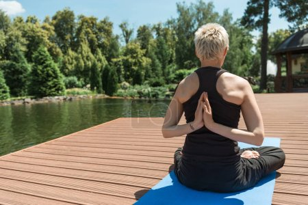 back view of woman practicing yoga in lotus pose and hands in namaste gesture on yoga mat near river in park