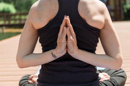 Photo pour Image recadrée de femme pratiquant l'yoga en posture de lotus et les mains en geste de namaste dans le parc - image libre de droit