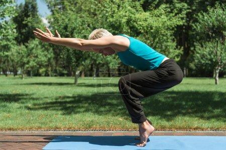 Photo pour Vue latérale de la femme pratiquant le yoga sur tapis de yoga dans le parc - image libre de droit