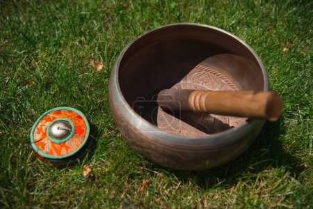 tibetan singing bowl on green grass in park