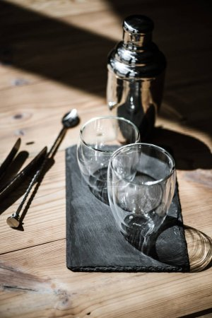 close-up view of empty glasses on slate board, shaker and tongs on wooden table