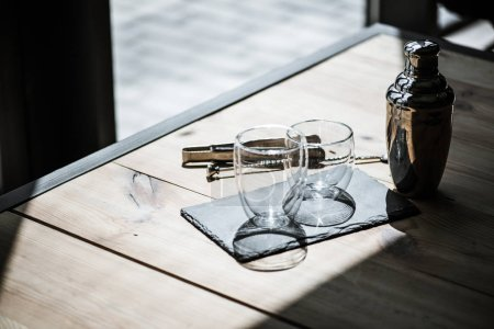 high angle view of shiny empty glasses on slate board, shaker and tongs on wooden table