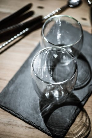 close-up view of shiny empty glasses on slate board on table