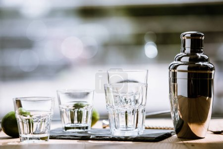 close-up view of shiny shaker, empty glasses and fresh limes on wooden table