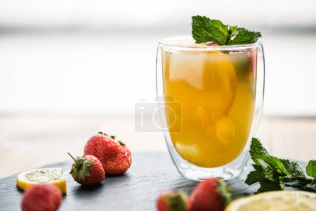 close-up view of glass with juicy summer cocktail with mint and strawberries