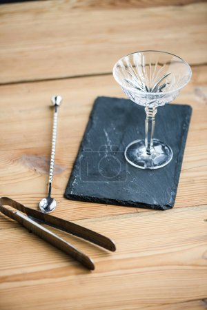 close-up view of margarita glass on slate board and tongs on wooden table