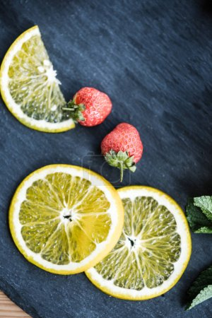 top view of fresh sliced lemon and ripe strawberries on slate board