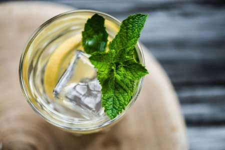 top view of cold fresh summer cocktail with mint and ice cubes in glass