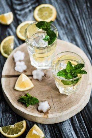 Photo pour Vue grand angle du cocktail de mojito frais froid dans des verres sur la surface en bois - image libre de droit