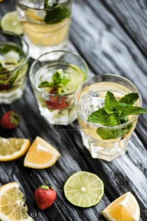 close-up view of fresh cold summer cocktails in glasses on wooden table