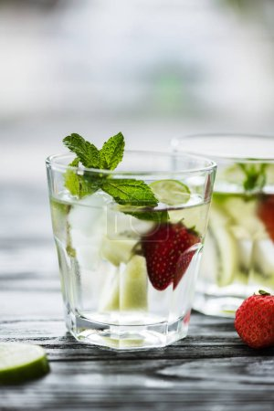 delicious strawberry mojito cocktail in glasses on wooden table