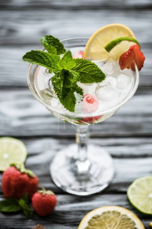 close-up view of fresh strawberry mojito cocktail in glass on wooden table
