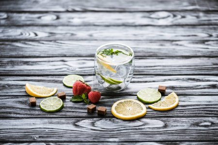 fresh cold lemonade in glass and ripe ripe strawberries on wooden table