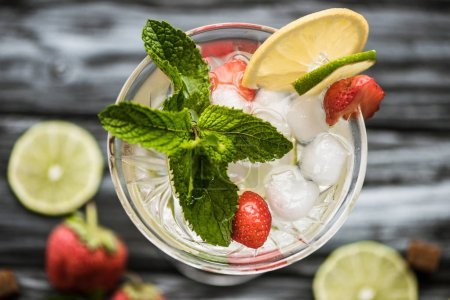 top view of cold strawberry mojito cocktail with mint and ice cubes in glass
