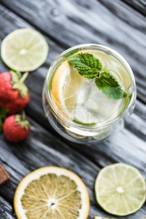close-up view of fresh cold mojito in glass on wooden table