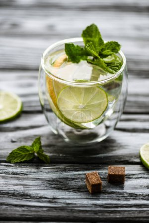 high angle view of glass with fresh cold mojito cocktail on wooden table