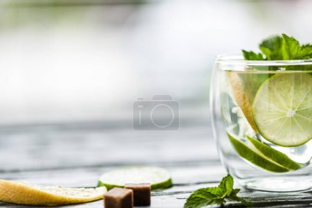 close-up view of glass with fresh cold mojito cocktail on table