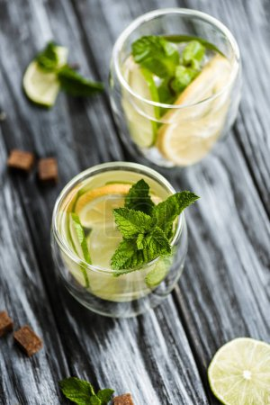 Photo pour Vue grand angle de frais froid mojito cocktail dans les verres sur la table en bois - image libre de droit