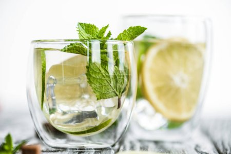 selective focus of fresh cold mojito cocktail in glasses on wooden table