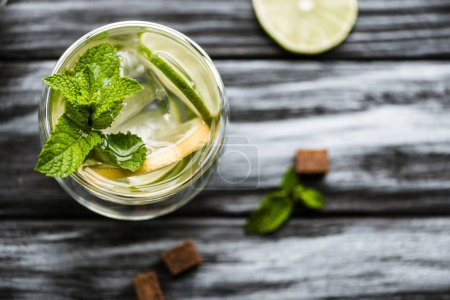 top view of fresh cold mojito cocktail in glass on wooden table