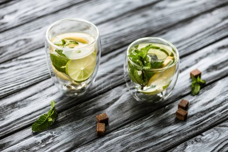 high angle view of glasses with cold fresh mojito on wooden table