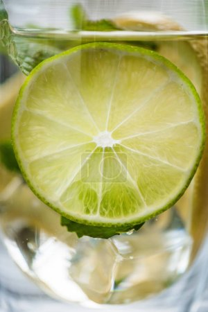 Photo for Close-up view of glass with cold fresh mojito and slice of lime - Royalty Free Image