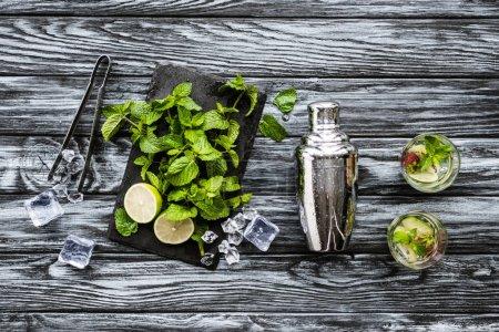 Draufsicht auf frische Minze, Zange, Shaker und Erdbeer-Kiwi-Mojito im Glas