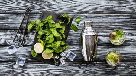 top view of fresh mint, tongs, shaker and strawberry kiwi mojito in glasses on wooden table