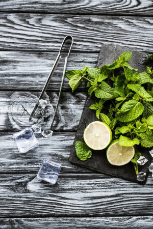 top view of ingredients for making mojito, ice cubes and tongs on wooden surface