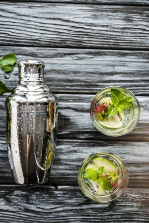 Photo for Top view of shaker and strawberry kiwi mojito in glasses on wooden table - Royalty Free Image