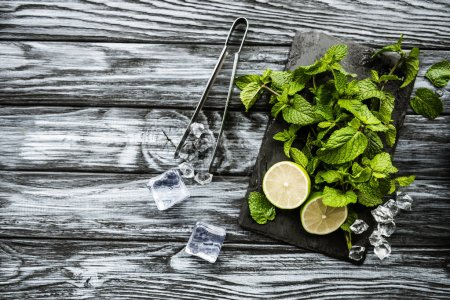 top view of ingredients for making mojito and tongs on wooden surface
